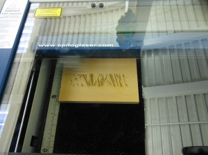 Kathleen monitors the laser cutter while it engraves a bark pattern in yellow cedar.